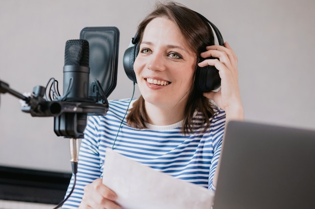 The stylish and educated caucasian woman records podcasts in a recording studio or in her home