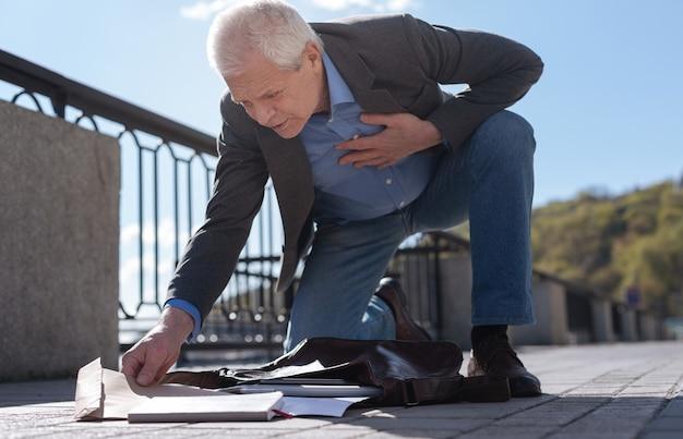 Стильный пожилой умный пенсионер собирает разбросанные вещи в сумке и удивляет, обнаруживая интересный конверт