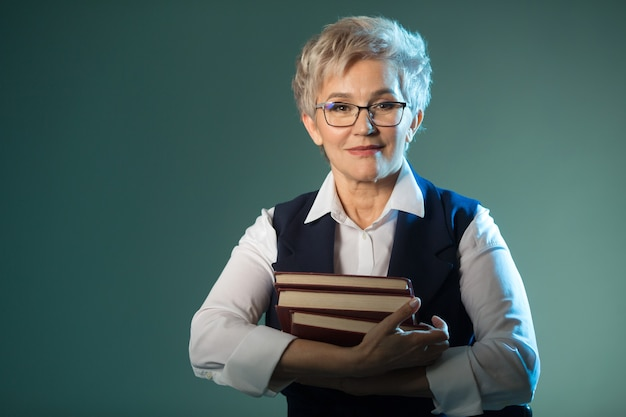 Stylish elderly woman in glasses with books in their hands