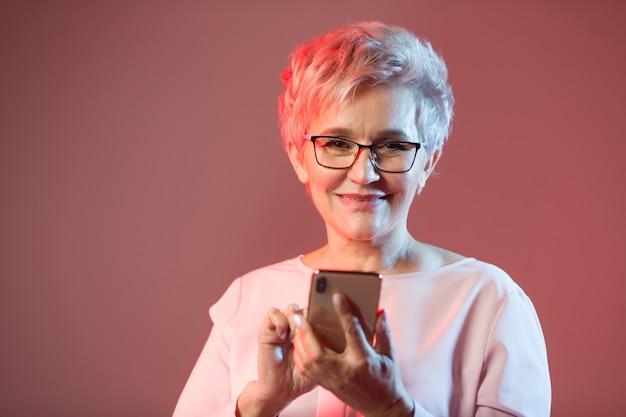 Стильная пожилая женщина в очках с телефоном в руке