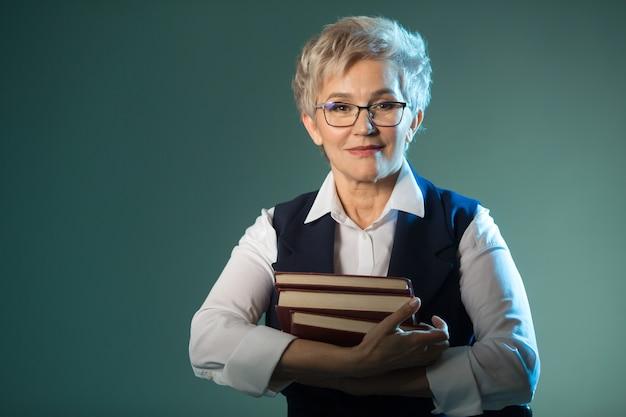Стильная пожилая женщина в очках с книгами в руках