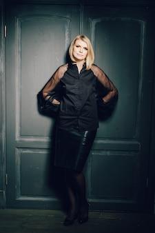 木製のドアのオフィススタイルの背景に黒いシャツと革のスカートでスタイリッシュなエレガントな美しい若い女性。