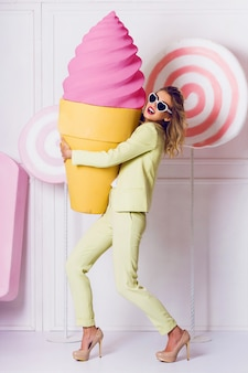 Stylish elegant blonde woman posing in studio with sweets in casual pastel  suit . candy  and macaroons objects  background. soft pastel  colors.