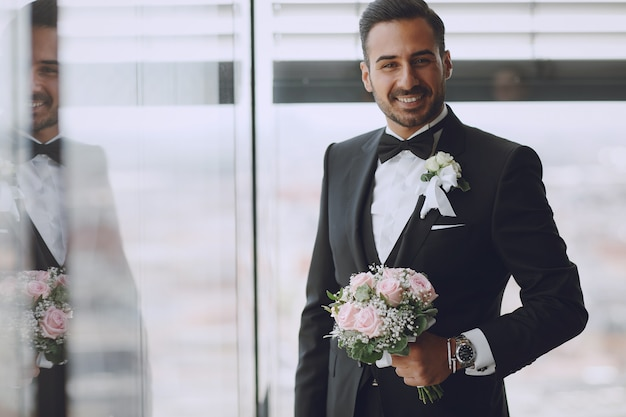 The stylish and elegant bridegroom is in the hotel room with a bouquet of flowers