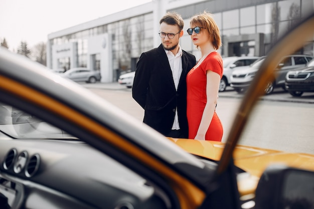 Stylish and elegant couple in car salon