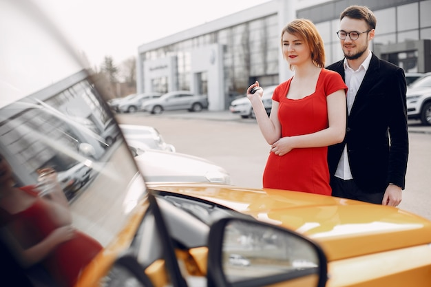 Stylish and elegant couple in car salon