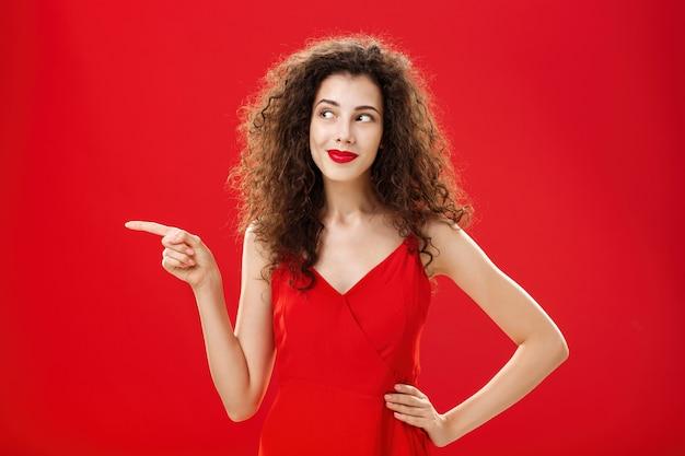 Elegante ed elegante donna affascinante curiosa con l'acconciatura riccia in rossetto rosso e vestito alla moda che tiene la mano sull'anca che punta e sembra a sinistra deliziata e interessata sullo sfondo dello studio.
