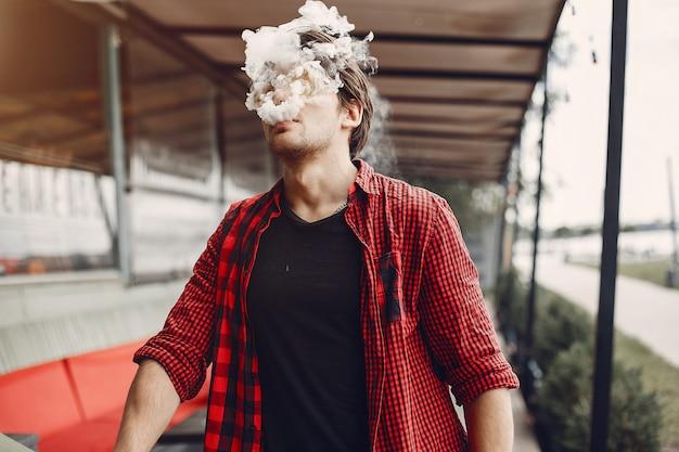 Uomo elegante e alla moda in una città con vaporizzatore Foto Gratuite