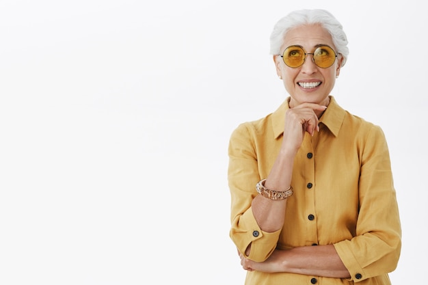 Stylish and elegant old woman in sunglasses looking up thoughtful and smiling