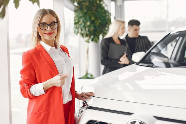Stylish and elegant people in a car salon