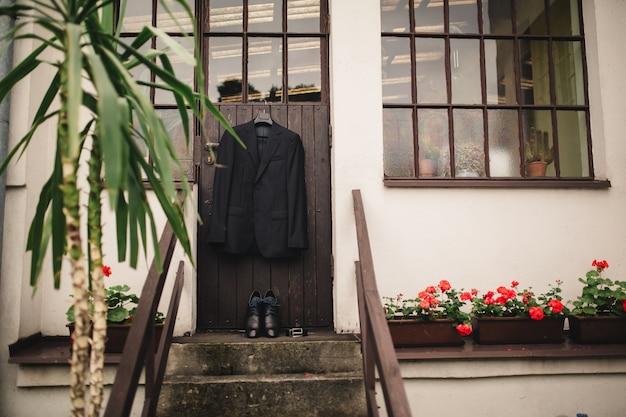 Stylish elegant wedding groom suit with buttonhole hanging on wooden.
