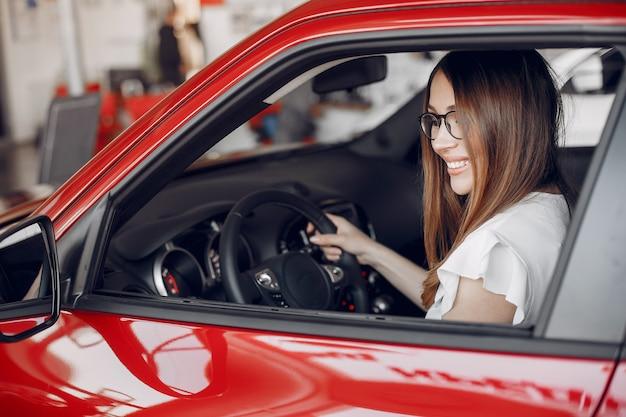 Elegante ed elegante donna in un salone di auto Foto Gratuite