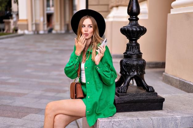 Стильная элегантная женщина позирует в центре европейского города, в ярком льняном зеленом костюме и черной шляпе, в стиле летних каникул.