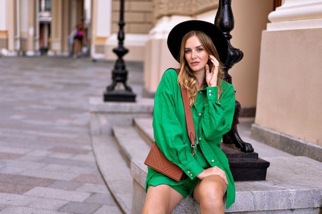 Стильная элегантная женщина позирует в центре европейского города, в ярком льняном зеленом костюме и черной шляпе