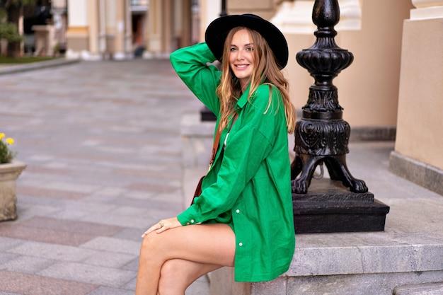 Elegante donna elegante in posa al centro della città europea, che indossa un abito di lino verde brillante e un cappello nero, stile di vacanza estiva.