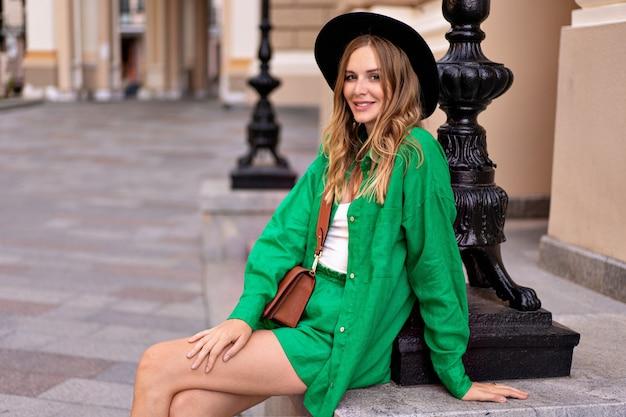 Стильная элегантная женщина позирует возле старого здания парижа, в модном летнем льняном костюме и шляпе, в стиле уличной моды.