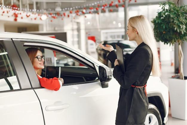 Donne eleganti e alla moda in un salone di auto
