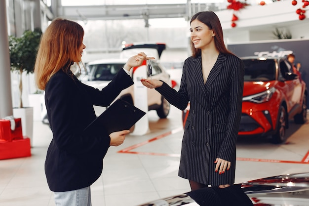 Stylish and elegant women in a car salon