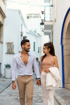 Stylish ethnic couple walking in old town