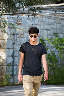 Stylish ethnic teen man in sunglasses walking on street