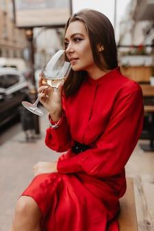 Стильный европейский пьет вкусное белое вино в уличном ресторане. красивый макияж выгодно подчеркивает все достоинства молодой девушки, позирующей портрету.