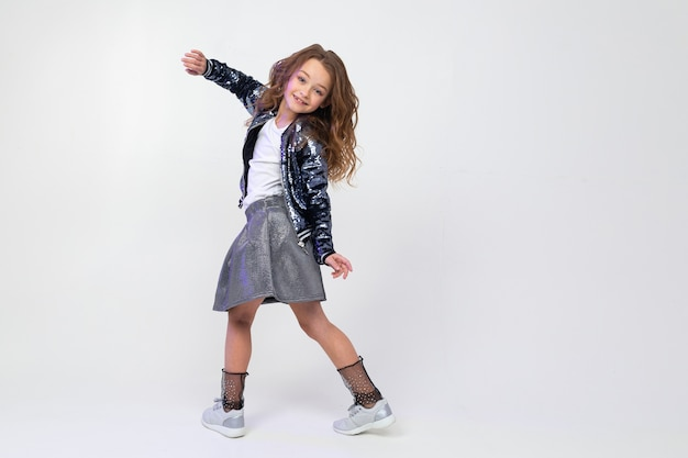 Stylish european girl in a beautiful image dances in full growth on a light studio background with copy space.