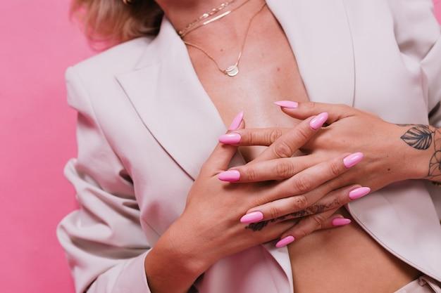 Стильная европейская женщина в элегантном бежевом пиджаке и золотых украшениях, розовых ярких гелевых ногтях, позирует