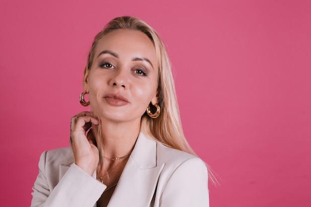 우아한 베이지색 블레이저와 황금 보석, 예쁜 화장과 큰 입술, 포즈를 취하는 세련된 유럽 여성