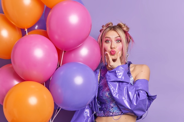 Stylish european woman keeps lips folded dressed in fashionable jacket shows demonstrates bare shoulder holds colorful inflated balloons decorates hall for party