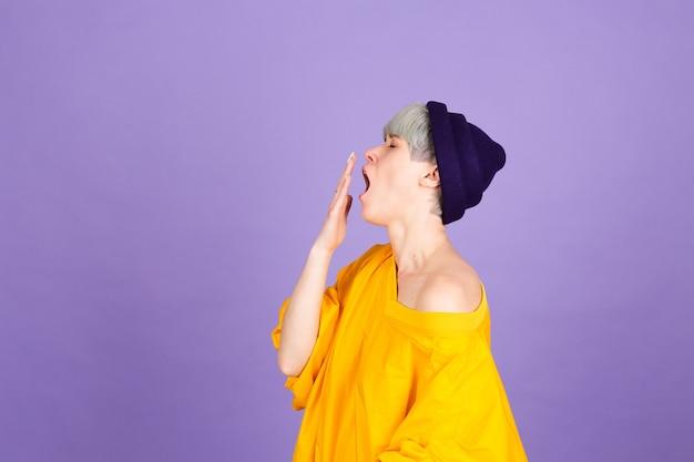 紫色の壁にスタイリッシュなヨーロッパの女性。手で口を覆う退屈なあくび疲れた Premium写真