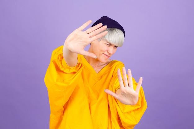 紫色の壁にスタイリッシュなヨーロッパの女性