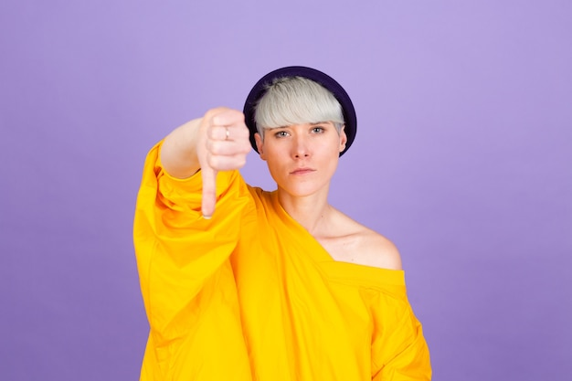 Stylish european woman on purple wall. looking unhappy and angry showing rejection and negative with thumbs down gesture. bad expression