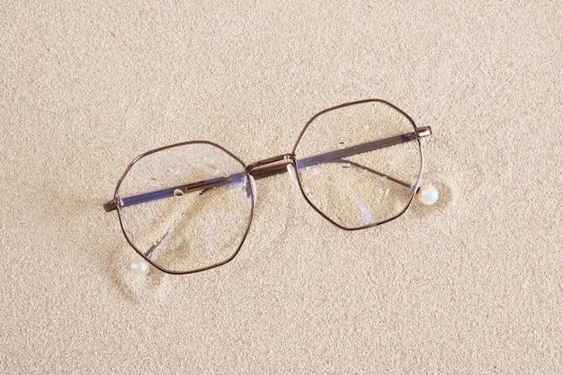 Стильные очки в круглой металлической оправе на песке, вид сверху