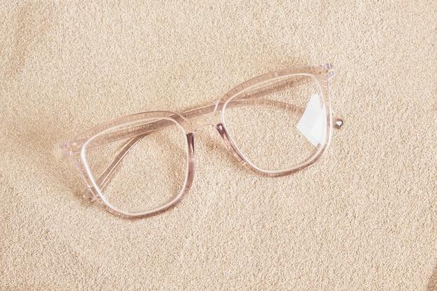 Стильные очки в прозрачной пластиковой оправе на копировальном пространстве вида сверху песка Premium Фотографии