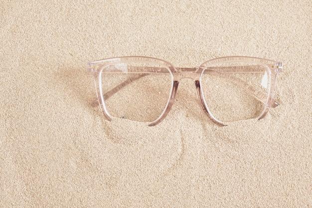 Стильные очки в прозрачной пластиковой оправе на копировальном пространстве вида сверху песка
