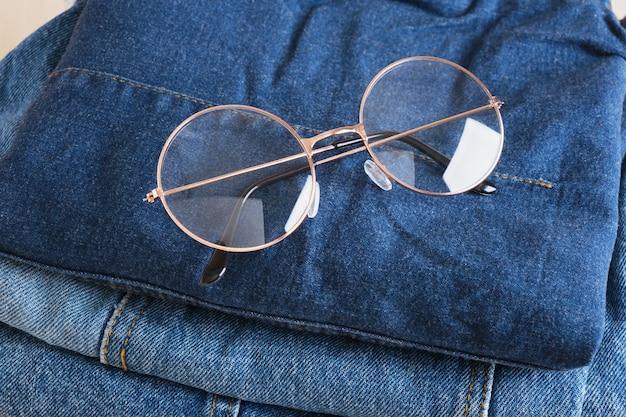 나무 배경 복사 공간에 있는 청바지 더미에 세련된 안경테 세련된 둥근 금속 프레임이 있는 탑 뷰 안경