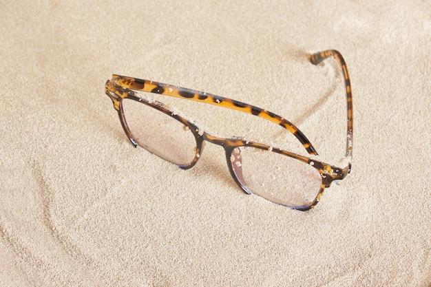 Стильные очки с пятнистой пластиковой оправой на песке, вид сверху копией пространства