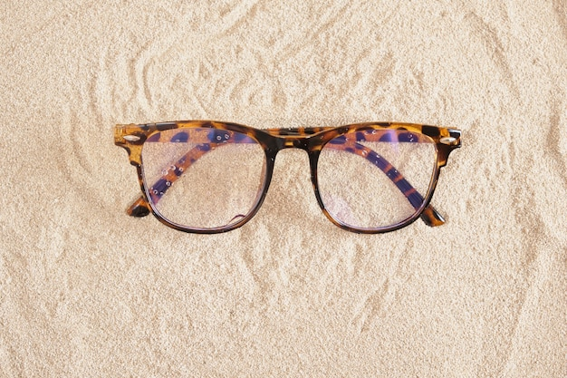 Стильные очки с пятнистой пластиковой оправой на песке, копией пространства