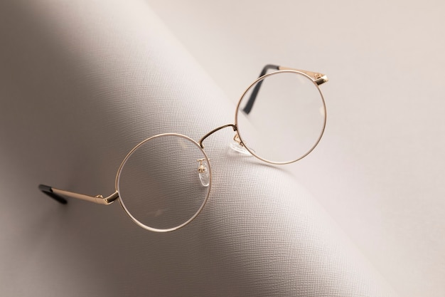 Stylish eyeglasses over gray  wall. optical store, glasses selection, eye test, vision examination at optician, fashion accessories concept
