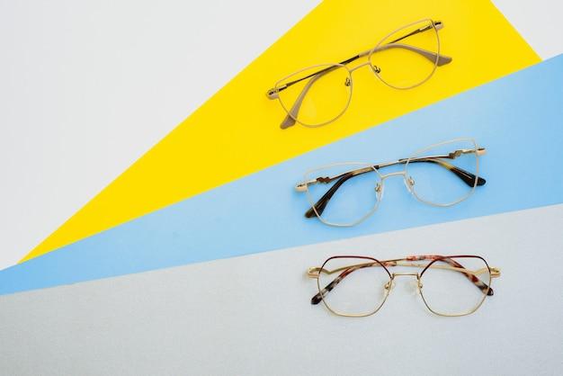 Стильные очки. современные оправы для очков на цветном фоне