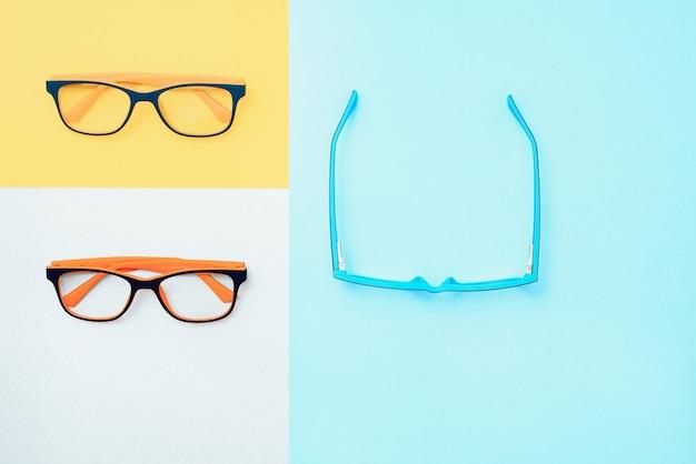 Стильные очки на фоне. магазин оптики, выбор очков, проверка зрения, проверка зрения в оптике, концепция модных аксессуаров. вид сверху, плоская планировка
