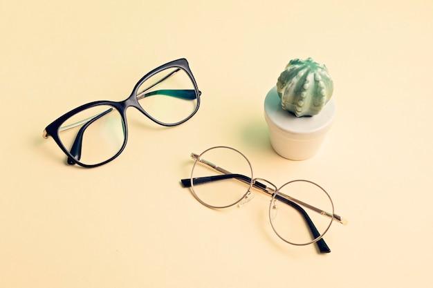 眼鏡技師、ファッションアクセサリーのコンセプトでパステル視力検査の上のスタイリッシュな眼鏡