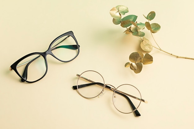Стильные очки над пастельной стеной. магазин оптики, выбор очков, проверка зрения, проверка зрения в оптике, концепция модных аксессуаров. вид сверху, плоская планировка
