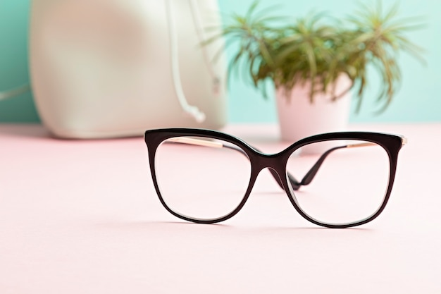 Stylish eyeglasses over pastel  wall. optical store,  eye test, vision examination at optician, fashion accessories concept. front view