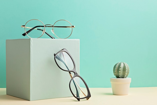 Stylish eyeglasses over pastel  wall. optical store, glasses selection, eye test, vision examination at optician, fashion accessories concept. front view