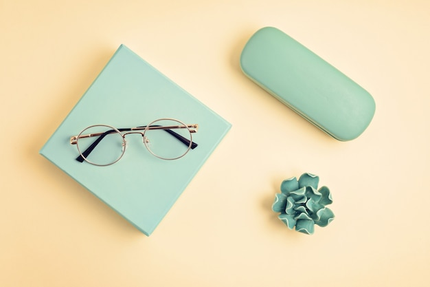 Stylish eyeglasses over pastel  wall. optical store, glasses selection, eye test, vision examination at optician, fashion accessories concept. top view, flat lay