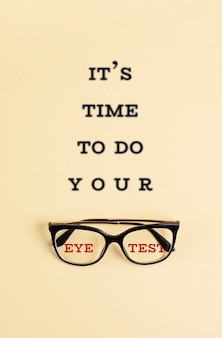 Stylish eyeglasses with the blurred text it is time to do your eye test. optical store, glasses selection, eye test, vision examination at optician, fashion accessories concept. top view, flat lay