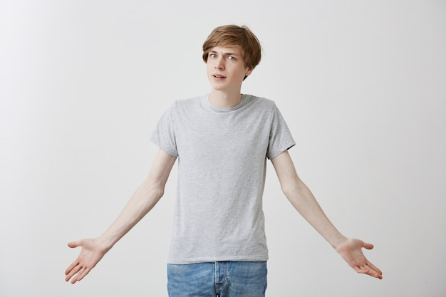 Stylish fair-haired caucasian guy in casual clothes, with blue eyes, shrugging shoulders with uncertainty, not knowing what to do next, isolated . puzzled and shocked man