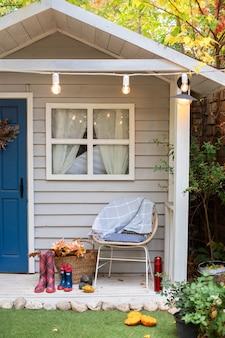 フロントベランダの家のスタイリッシュな秋の装飾。秋の木製ポーチの家。椅子、格子縞、ゴム長靴、菊のバスケットが付いた居心地の良いテラス。