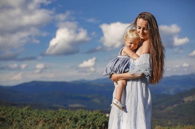 山の中のスタイリッシュな家族。空の背景にママと娘。白いドレスを着た女性。